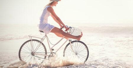 Kobieta wjeżdżająca rowerem do morza - zdrowe i piękne nogi na lato