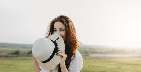 Młoda kobieta z kapeluszem na tle łąki - jak dbać o włosy latem
