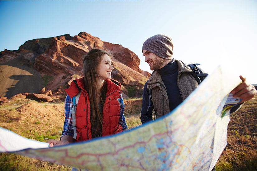 Para młodych ludzi w górach z mapą - co zabrać ze sobą w góry