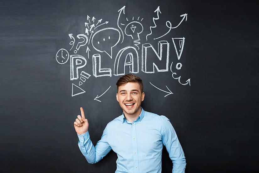 Mężczyzna na tle tablicy z napisem plan - powrót do rzeczywistości po urlopie