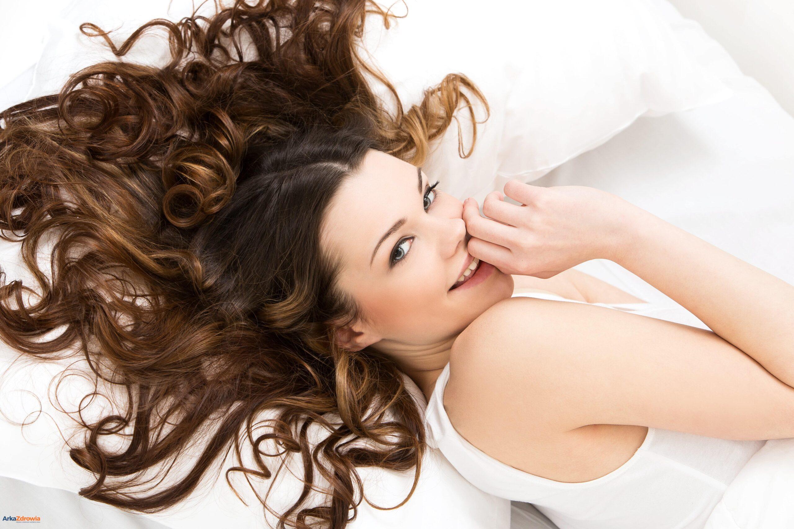 Uśmiechnięta młoda kobieta leżąca w łóżku - kwas hialuronowy dla zdrowia i urody