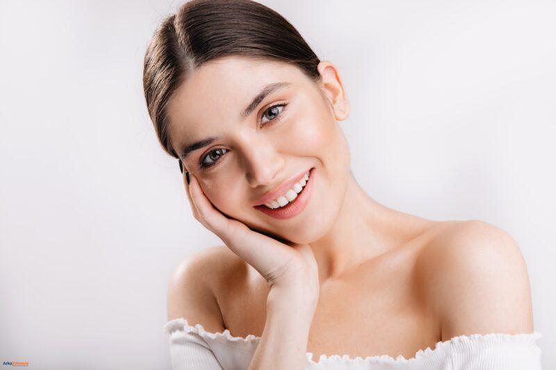 Uśmiechnięta młoda kobieta trzymająca dłoń na twarzy - jak zadbać o skórę po zimie