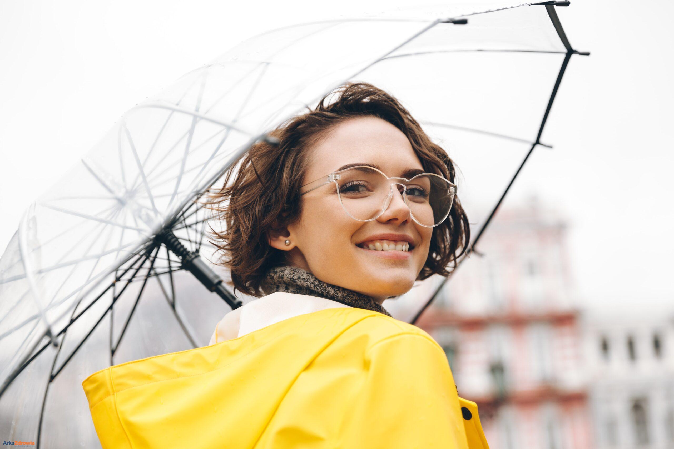 Uśmiechnięta młoda kobieta pod parasolem - już wiosną zacznij budować odporność na kolejny sezon jesienno-zimowy