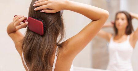 Kobieta czesząca włosy - najczęstsze problemy z włosami i sposoby na ich rozwiązanie